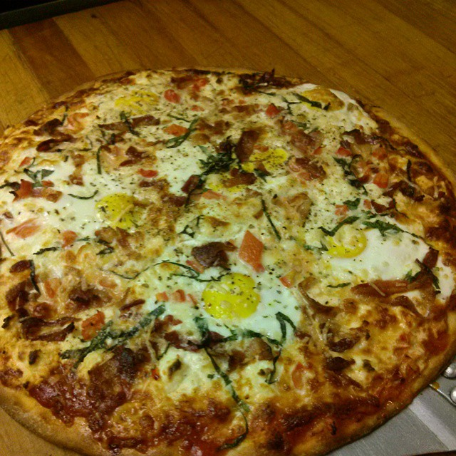 Why Not Breakfast Pizza topped with fresh cracked eggs, bacon, tomatoes and onions. - from Instagram